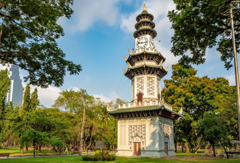 Torre de reloj asiática hermosa entre árbol verde fresco en parque en fondo del cielo azul imagenes de archivo