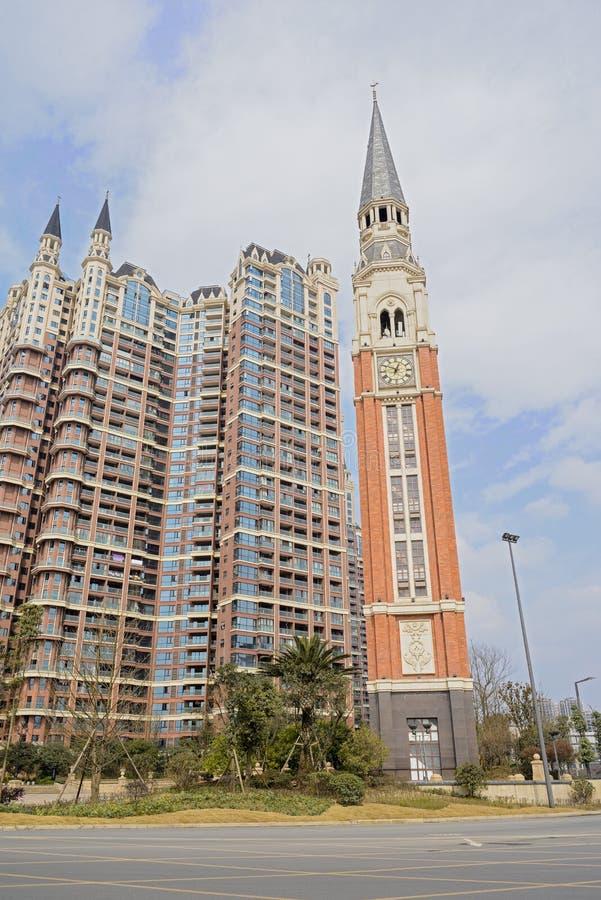 Torre de reloj del borde de la carretera y edificio moderno con las agujas en nublado fotografía de archivo