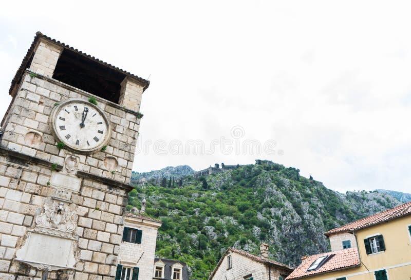 Torre de reloj en el cuadrado de los brazos, con las montañas en el fondo Kotor, Montenegro Edificio de piedra de la arquitectura foto de archivo libre de regalías