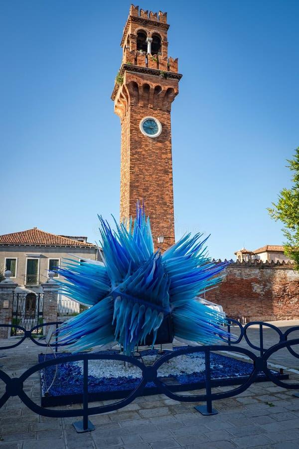 Torre de reloj de la iglesia de San Stefano y del cometa de la escultura del vidrio, Murano, Italia foto de archivo