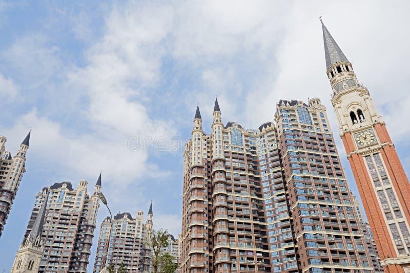 Torre de reloj y edificios modernos contra el cielo soleado foto de archivo