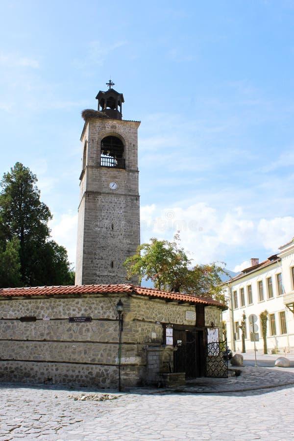 Torre de reloj y entrada de la iglesia en Bansko fotos de archivo