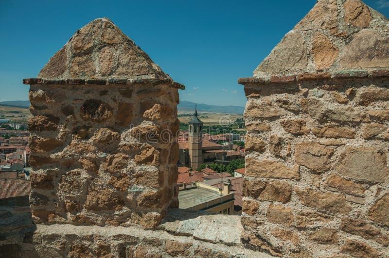 A torre de sino da igreja entre os telhados vistos de crenel em uma parede em Avila fotografia de stock royalty free