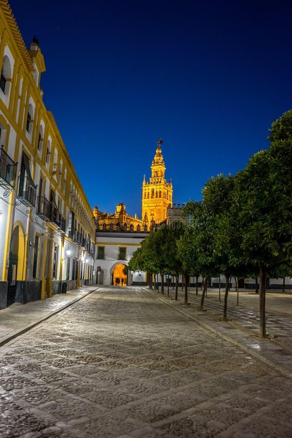 A torre de sino de Giralda iluminou-se acima na noite em Sevilha, Espanha, Europa foto de stock