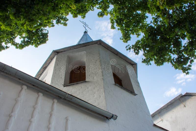 Torre de sino pequena e baixa perto da igreja com tijolos, branco pintado, com uma cruz cristã ortodoxo na parte superior no back imagem de stock royalty free