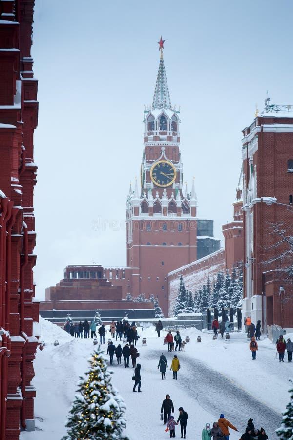 Torre de Spasskaya del invierno con el carillón, el árbol de navidad y la gente grandes en la Plaza Roja de Moscú después de gran imágenes de archivo libres de regalías