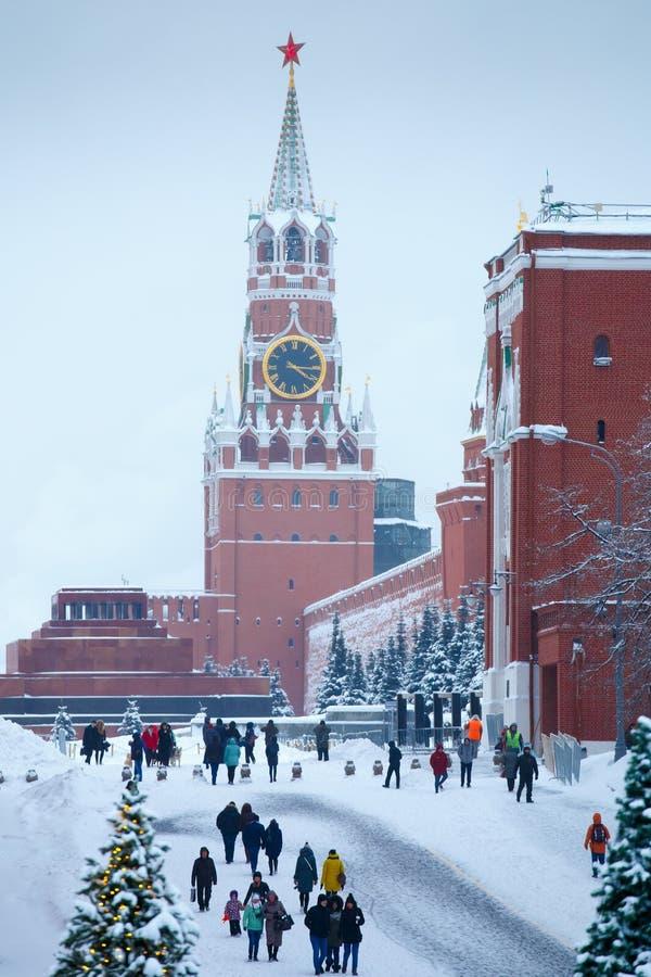 Torre de Spasskaya del invierno con el carillón, el árbol de navidad y la gente grandes en la Plaza Roja de Moscú después de gran foto de archivo libre de regalías