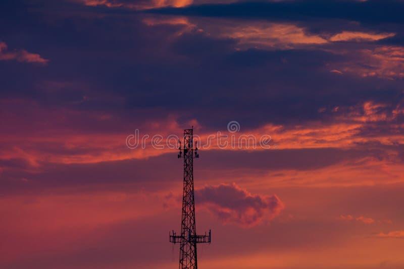 Torre de Telefone Celular Silhuetada Contra Nuvens Laranja e Roxa no Sunset fotografia de stock