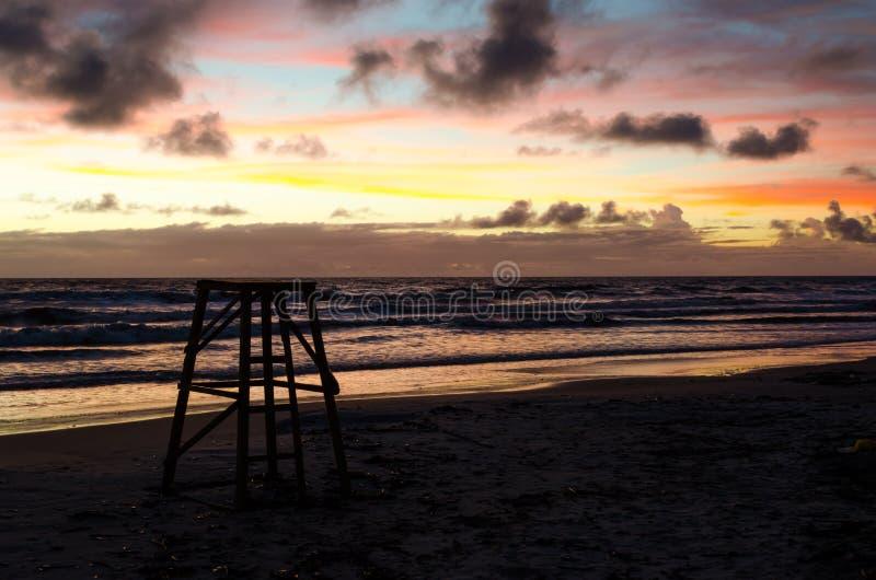 A torre de vigia da salva-vidas na silhueta em um nascer do sol em uma praia com sol colore o céu da pintura imagem de stock