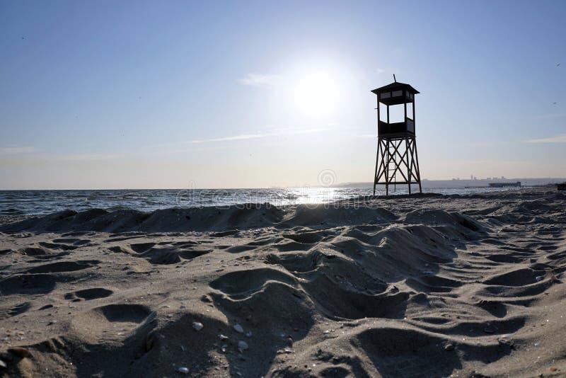 Torre del bagnino sulla spiaggia al giorno con cielo blu ed il fondo ondulato del mare fotografia stock libera da diritti