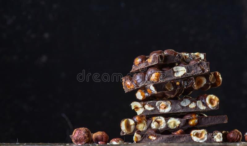 Torre del cioccolato con cacao ed i dadi, fondo culinario del cioccolato Pezzi fatti a mano del cioccolato con le spezie immagine stock