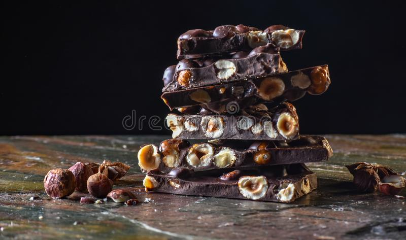 Torre del cioccolato con cacao ed i dadi, fondo culinario del cioccolato Pezzi fatti a mano del cioccolato con le spezie fotografia stock libera da diritti
