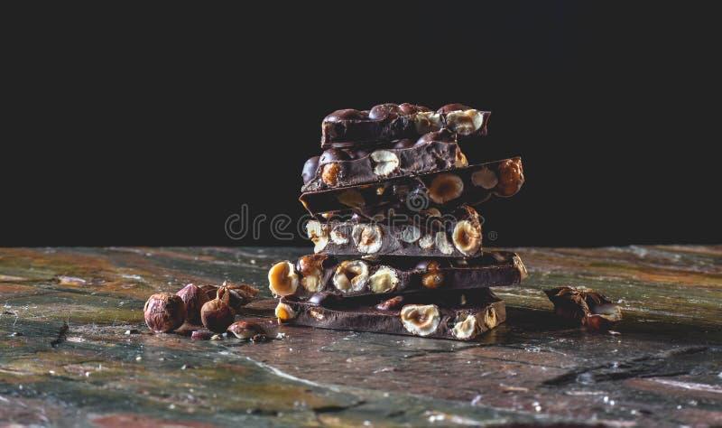 Torre del cioccolato con cacao ed i dadi, fondo culinario del cioccolato Pezzi fatti a mano del cioccolato con le spezie fotografia stock