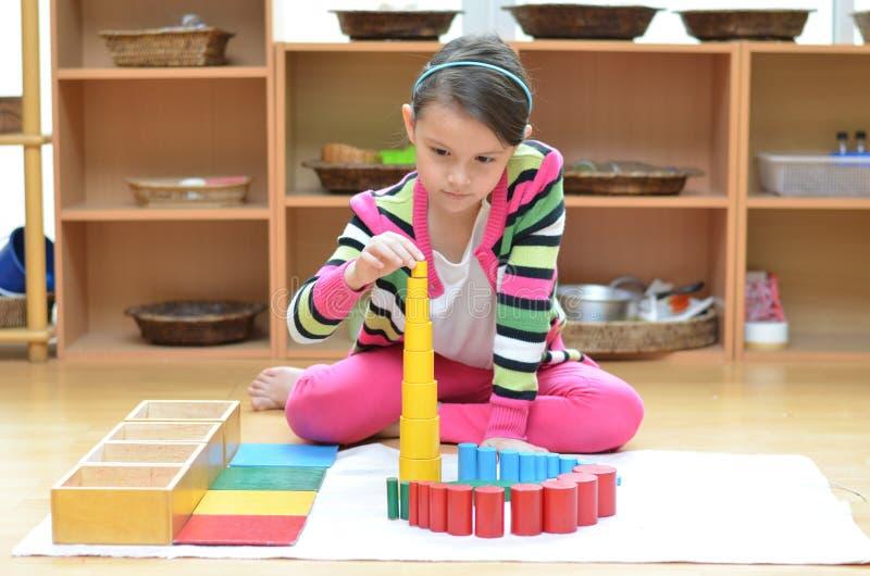 Torre del edificio de la mano de la niña hecha de montessori educativa foto de archivo libre de regalías