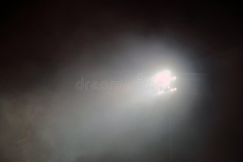 Torre del faro accesa ad uno stadio durante il nightime Indicatori luminosi dello stadio contro il fondo scuro del cielo notturno fotografia stock
