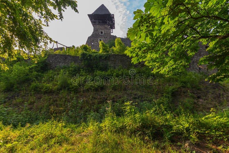 Torre del fortalecimiento en el fondo de una pared de piedra vieja, demasiado grande para su edad con la hierba verde imagen de archivo libre de regalías