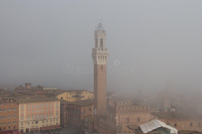 Torre Del Mangia in Piazza Del Campo und tupical Hinweis-Dächer von Siena im starken Nebel Toskana, Italien lizenzfreies stockbild