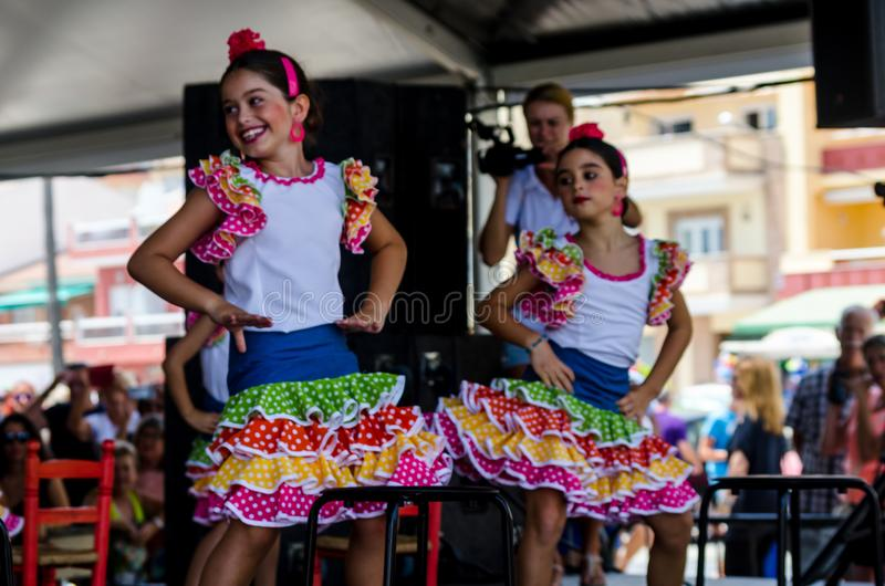 TORRE DEL MAR, SPAIN - JULY 22, 2018 Children dancing to the rhythm of typical Spanish flamenco music, dance group show royalty free stock photography