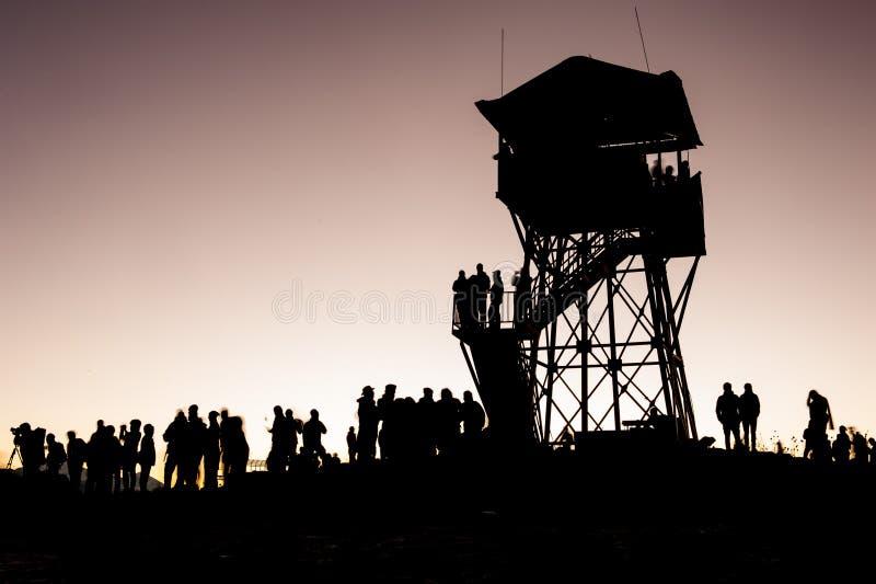 Torre del punto de opinión de Poonhill por la mañana antes de la salida del sol Siluetas de trekkers y de la torre del puesto de  fotografía de archivo