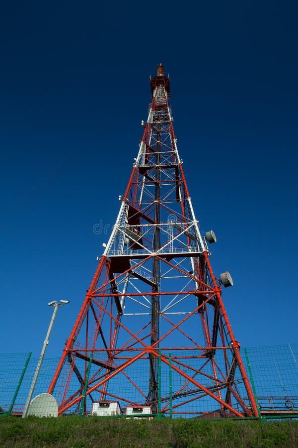 Torre de la difusión de las telecomunicaciones debajo del cielo azul foto de archivo libre de regalías