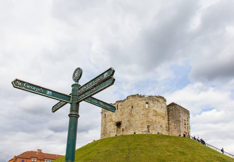 Torre del ` s de Clifford en York en hierba verde y señales de tráfico imagenes de archivo