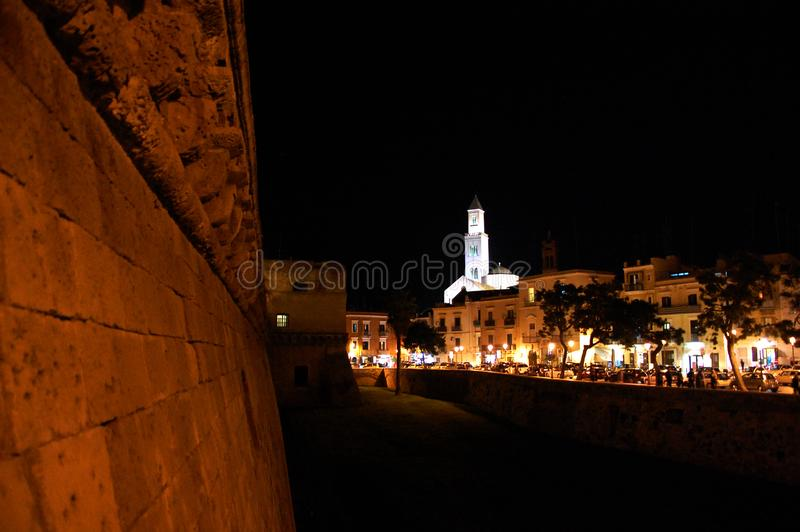 Torre dell'edificio servizi provinciale visto alla notte con le riflessioni delle luci nel mare adriatico dal castello medievale fotografia stock libera da diritti