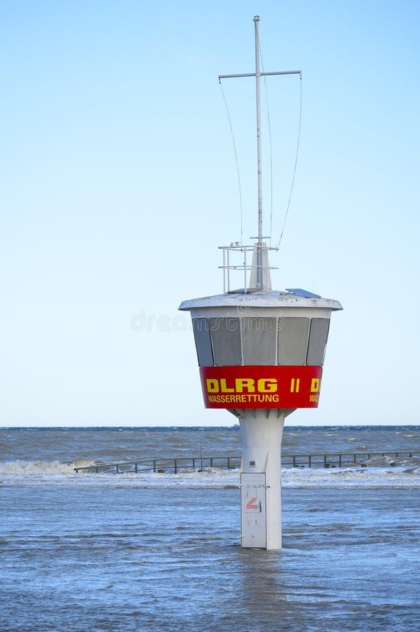 Torre dell'orologio della baia nella spiaggia sommersa ad alta marea contro un cielo blu in Travemuende, Mar Baltico, l'etichetta fotografia stock libera da diritti