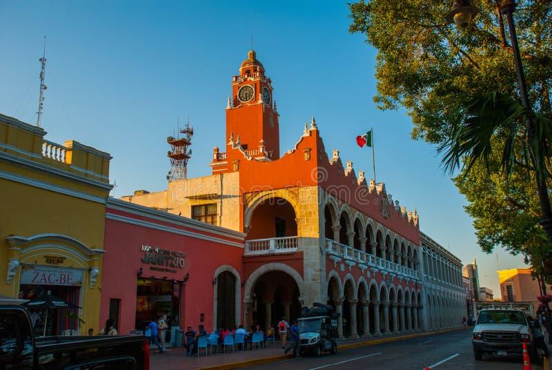 Torre della costruzione di mattone rosso con Golden Dome ed orologio nel centro urbano di Merida La bandiera messicana fluttua su fotografia stock libera da diritti