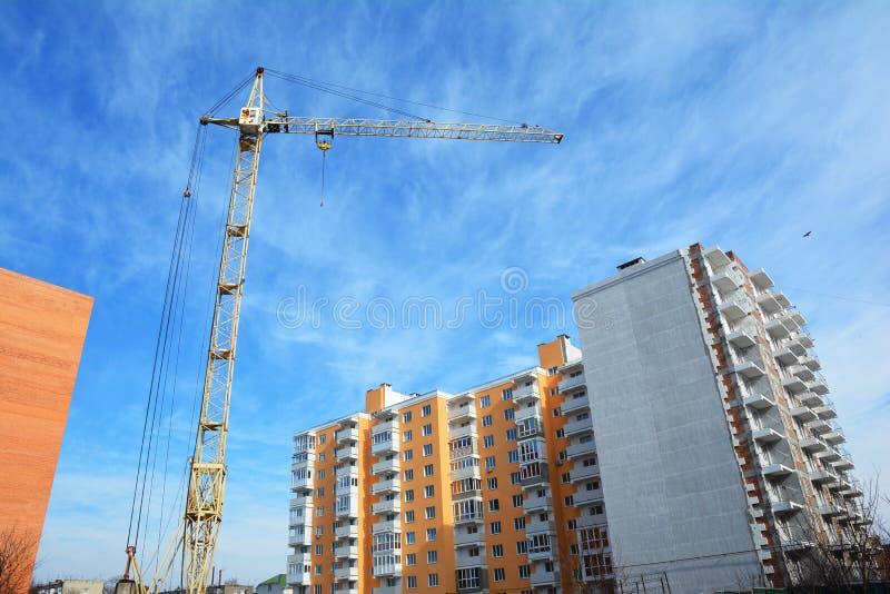 Torre della gru con il cantiere della casa di palazzo multipiano ed il cielo nuvoloso accogliente fotografie stock libere da diritti