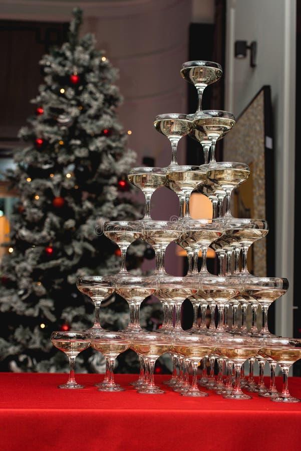 Torre di Champagne su una tavola rossa con l'albero di Natale nei precedenti fotografie stock