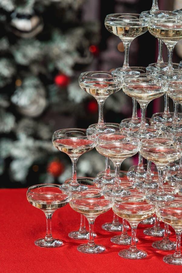 Torre di Champagne su una tavola rossa con l'albero di Natale nei precedenti immagine stock libera da diritti