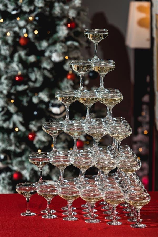 Torre di Champagne su una tavola rossa con l'albero di Natale nei precedenti fotografia stock libera da diritti