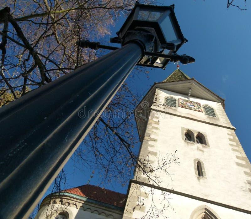 Torre di chiesa medievale con la lampada di via nel retro stile nella prospettiva estremamente ripida immagini stock libere da diritti