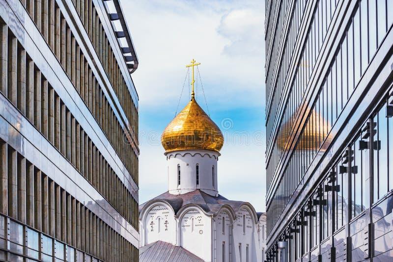 Torre di chiesa ortodossa fra due costruzioni moderne immagine stock