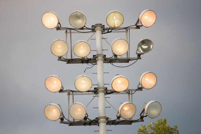 Torre di luci dell'inondazione dello stadio di sport accesa durante il gioco immagini stock libere da diritti