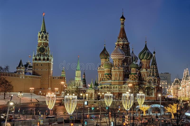 Torre di orologio di Cremlino e cattedrale della st Basil's incorniciata dalle iluminazioni pubbliche festive nella penombra fotografia stock