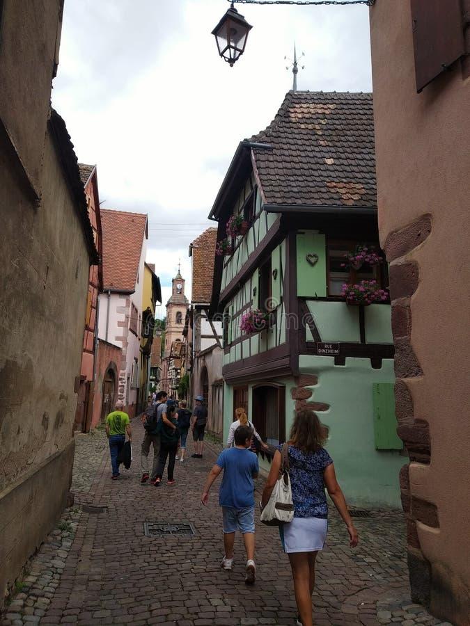 Torre di orologio e Camere tradizionali con le facciate variopinte e tetti pendenti in Riquewihr, Francia fotografie stock