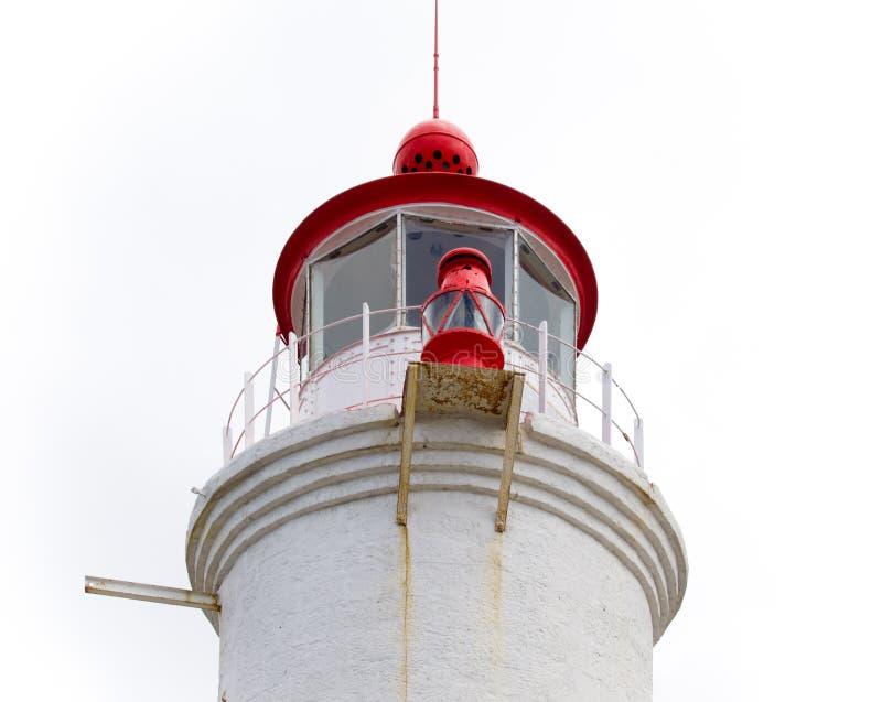 Torre di pietra cilindrica rossa e bianca di un faro con la lanterna e la galleria fotografia stock