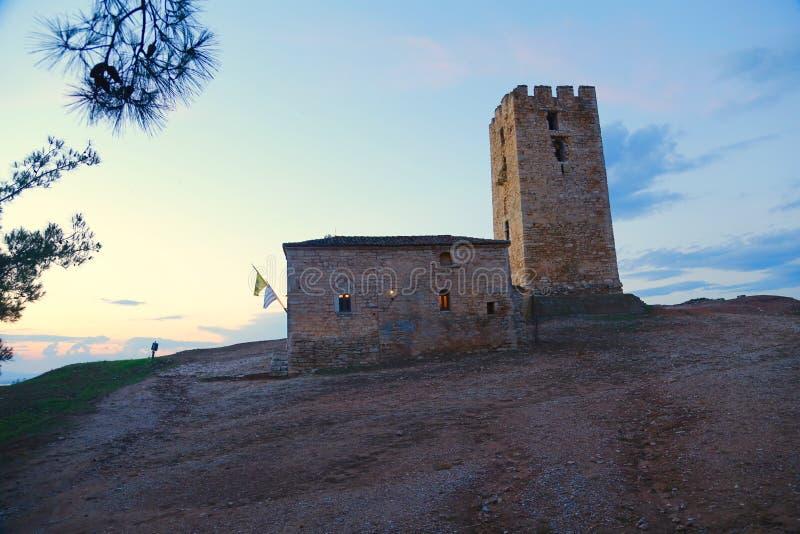 Torre di pietra e una casa sulla collina immagini stock libere da diritti