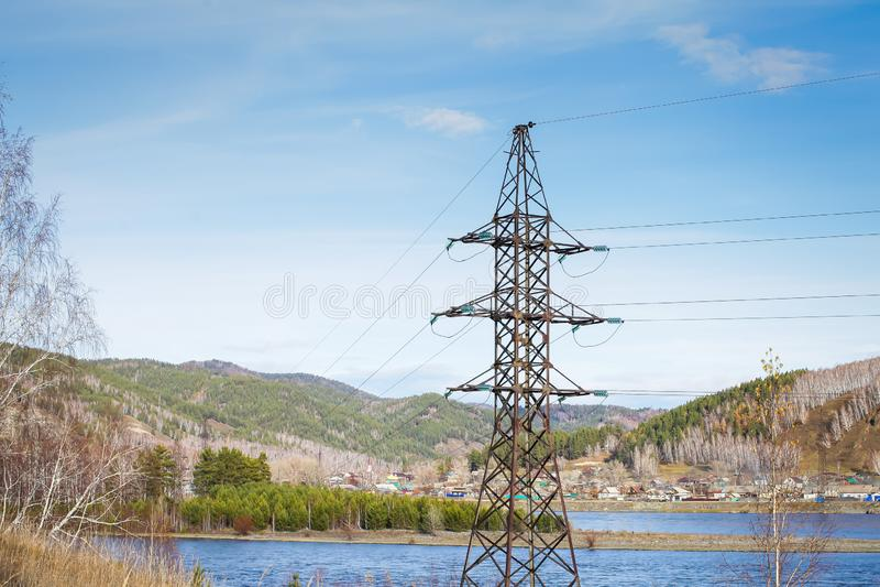 Torre di potere e linee elettriche ad alta tensione al giorno di autunno del brigth con cielo blu ed il fiume sui precedenti immagini stock libere da diritti