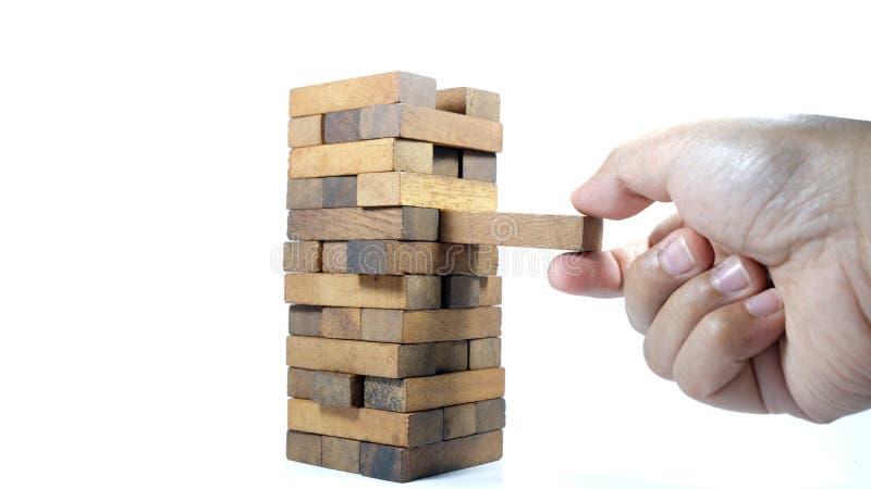 A torre dos blocos e da m?o de madeira do ` s do homem toma um bloco O jogo do close-up dos dados imagens de stock