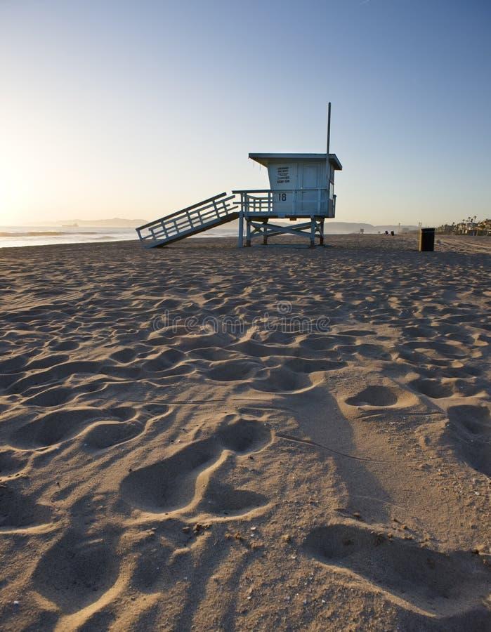 Torre e areia de protetor da vida no por do sol fotografia de stock royalty free