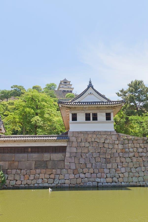 A torre e o cano principal do relógio mantêm-se do castelo de Marugame, Japão imagem de stock