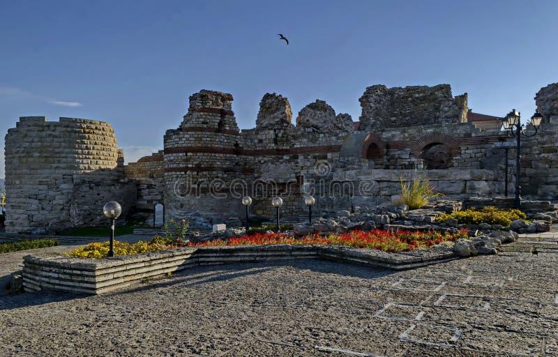 Torre e pietra rovinate dell'orologio con i mura di mattoni intorno alla fortificazione occidentale in città antica Nessebar o Me fotografie stock
