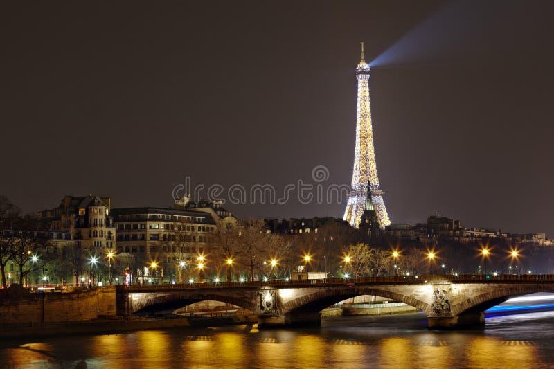 Torre Eiffel con la iluminación y DES Invalides de la noche de Pont imagen de archivo