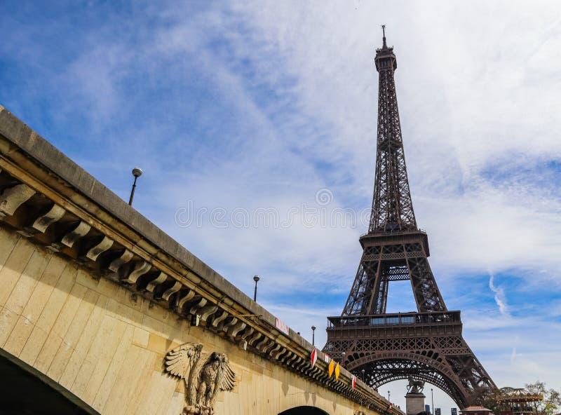 Torre Eiffel contra o c?u azul com nuvens e uma ponte sobre Seine River Paris France Em abril de 2019 imagens de stock royalty free