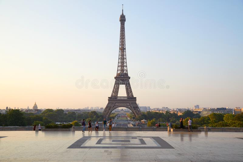 Torre Eiffel e la gente che camminano a Parigi alla luce solare calda di mattina immagine stock