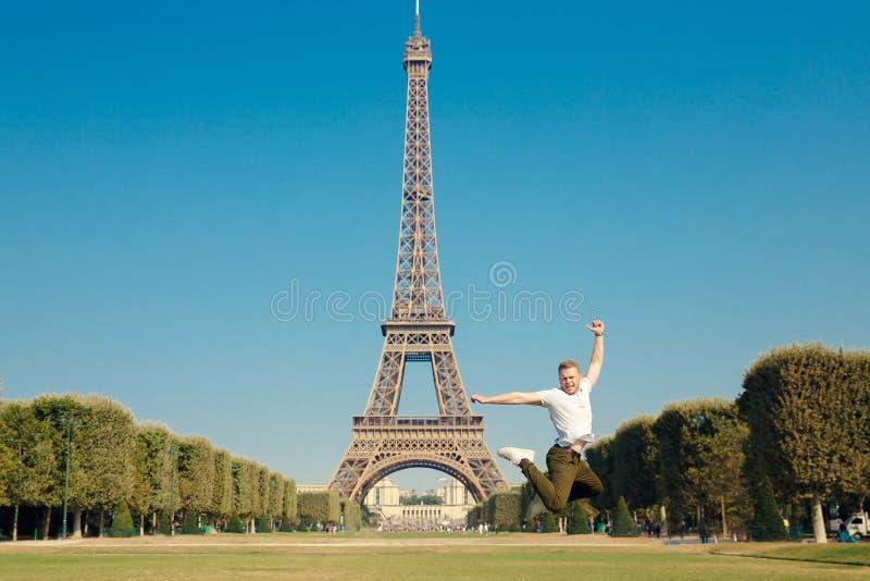 Torre Eiffel El individuo saltó encima del aire, manos a disposición D?a soleado caliente del oto?o Los árboles amarillos parquea imagen de archivo libre de regalías