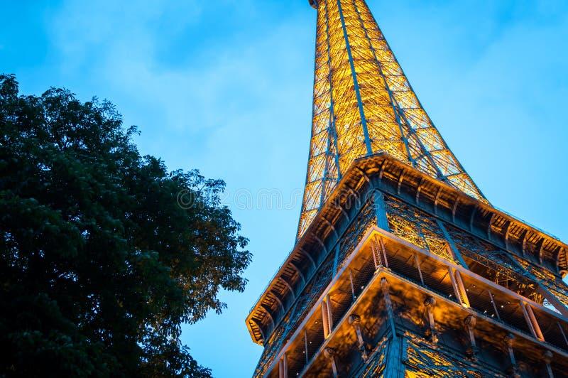 A torre Eiffel vista de baixo na noite em um céu noturno azul imagem de stock