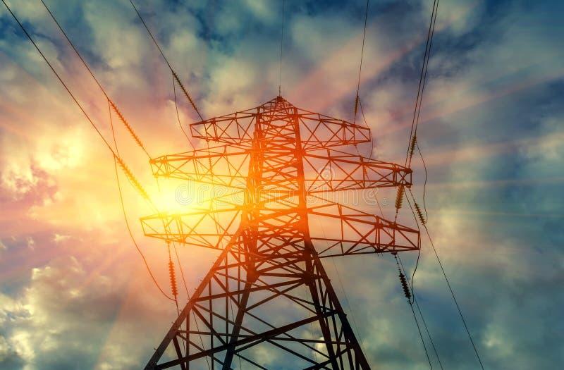 Torre eléctrica de alto voltaje de la transmisión en la puesta del sol fotos de archivo